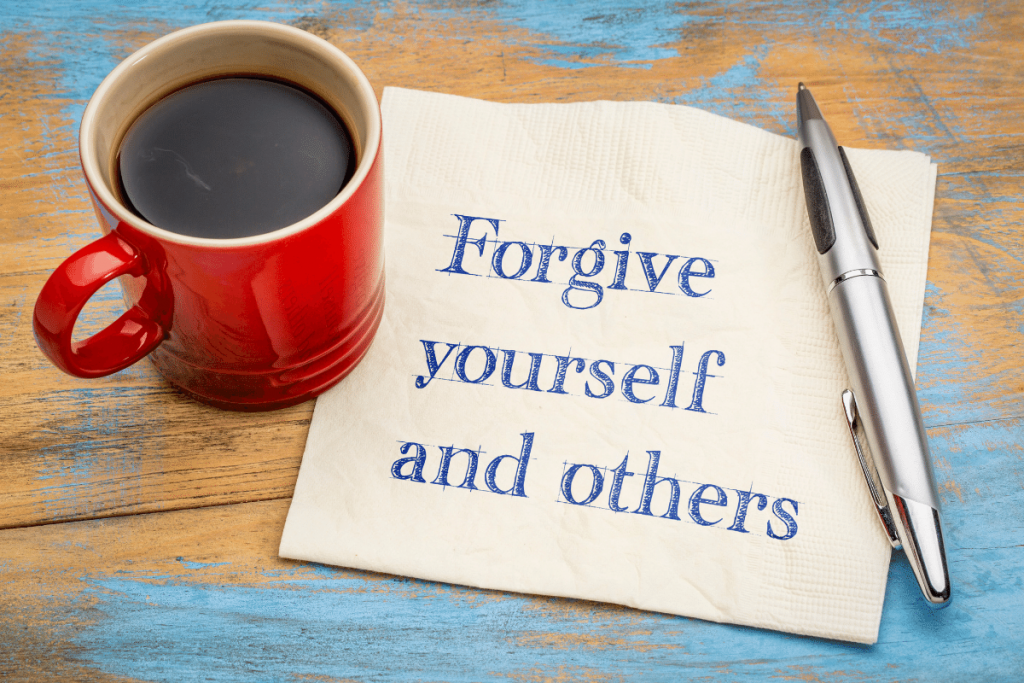 Forgive yourself and other note on a paper napkin , along with coffe on the side and a pen.