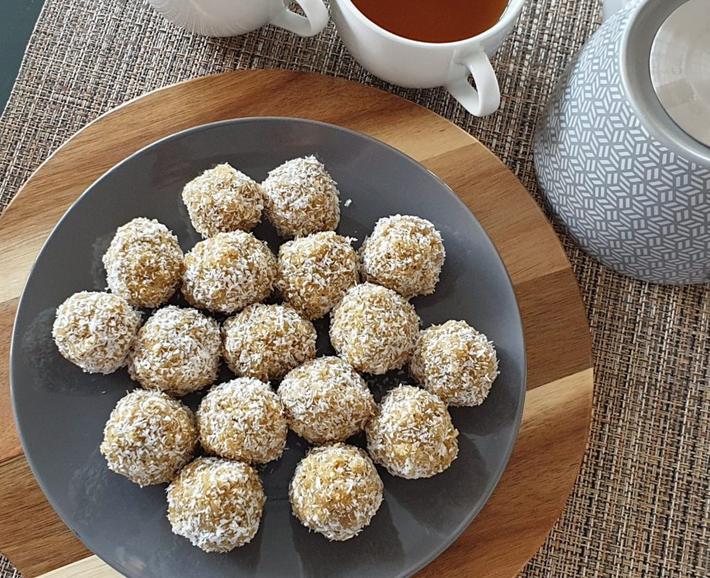 Coconut balls in a plate with tea in cups and a tea pot