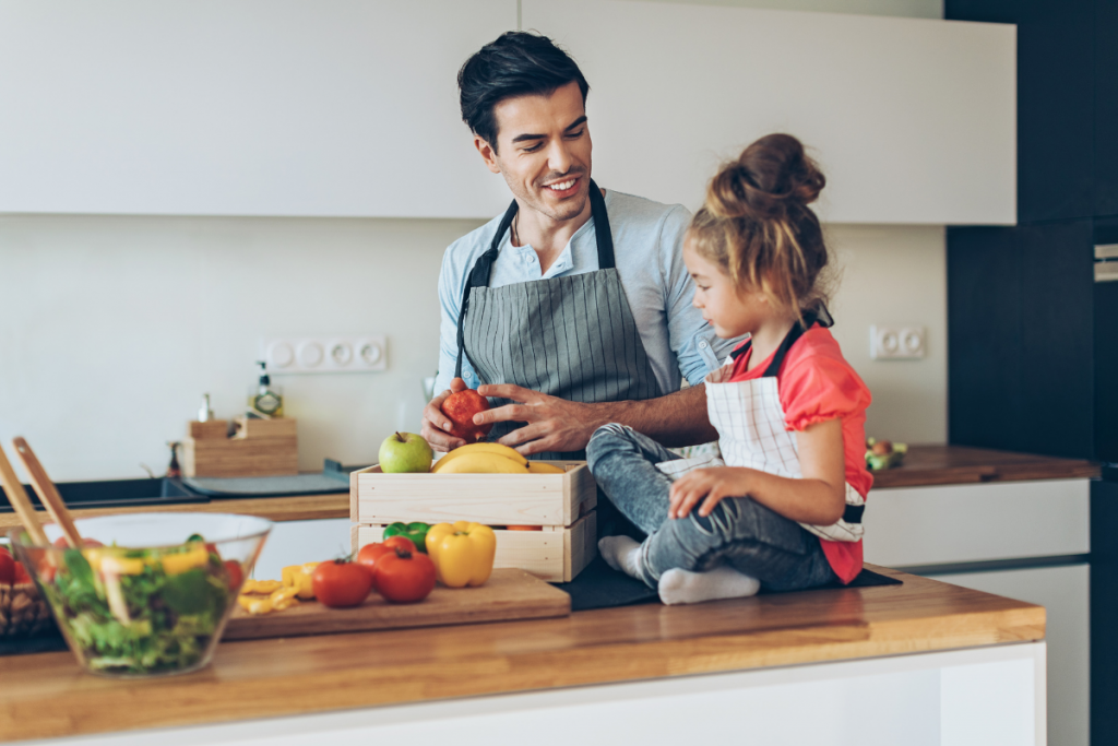 Father and daughter in the kitchen, developing healthy eating in kids