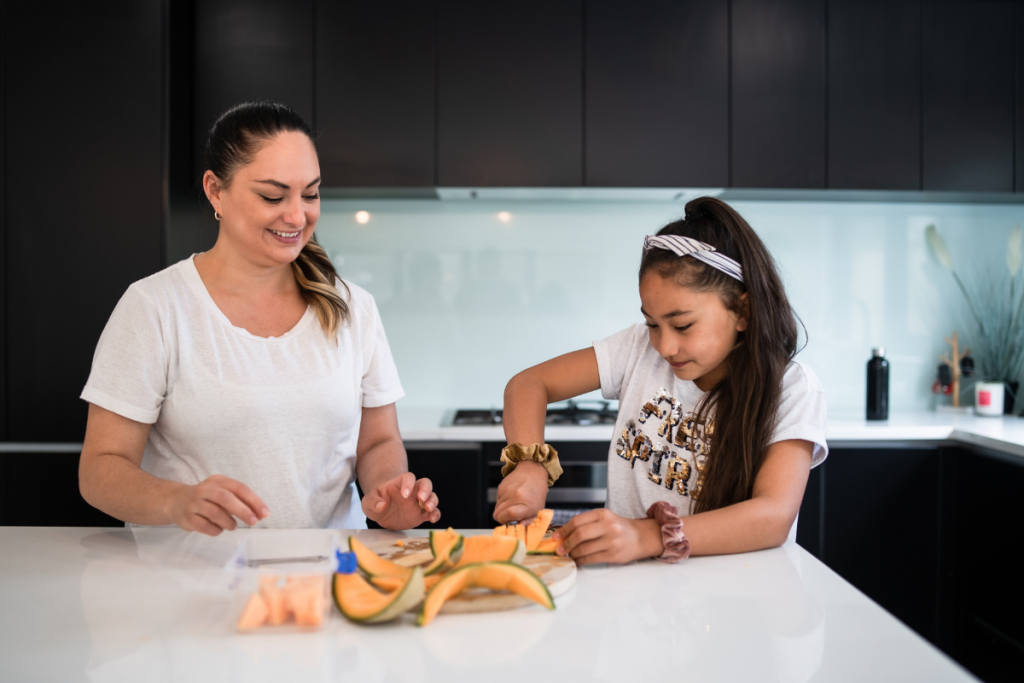 Mother showing daughter to cut fruits
