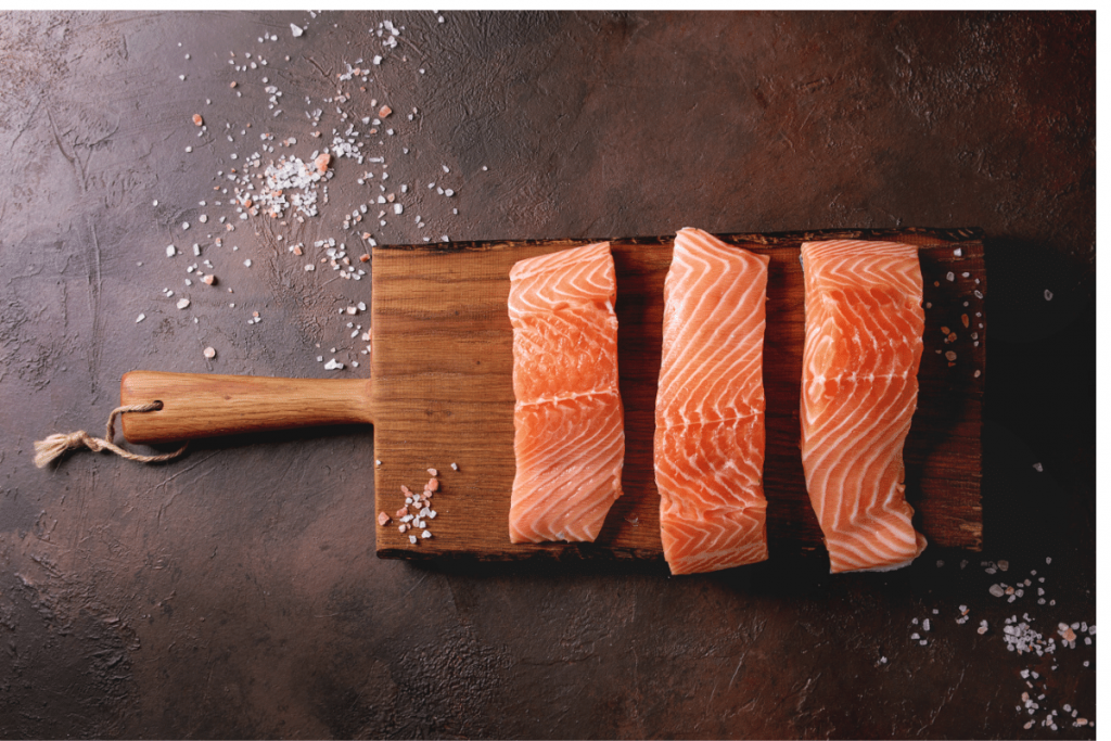 Salmon fillets on a board with salt