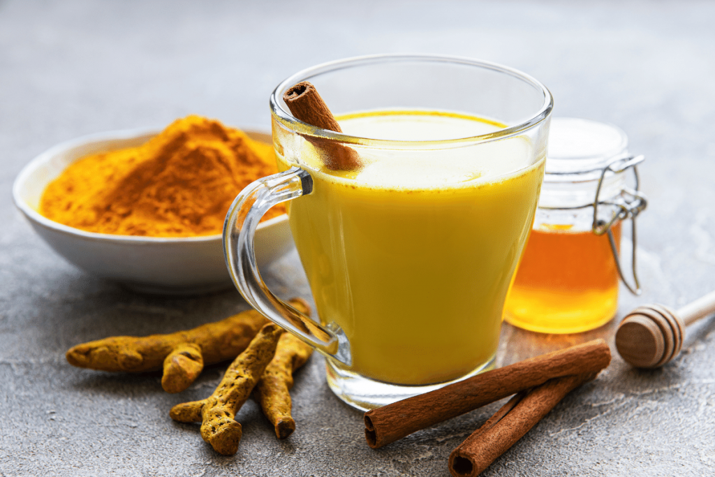 Turmeric milk with turmeric powder, root, cinnamon sticks and honey on the side