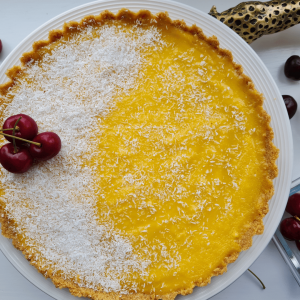 Lemon curd tart with cherries and desiccated coconut