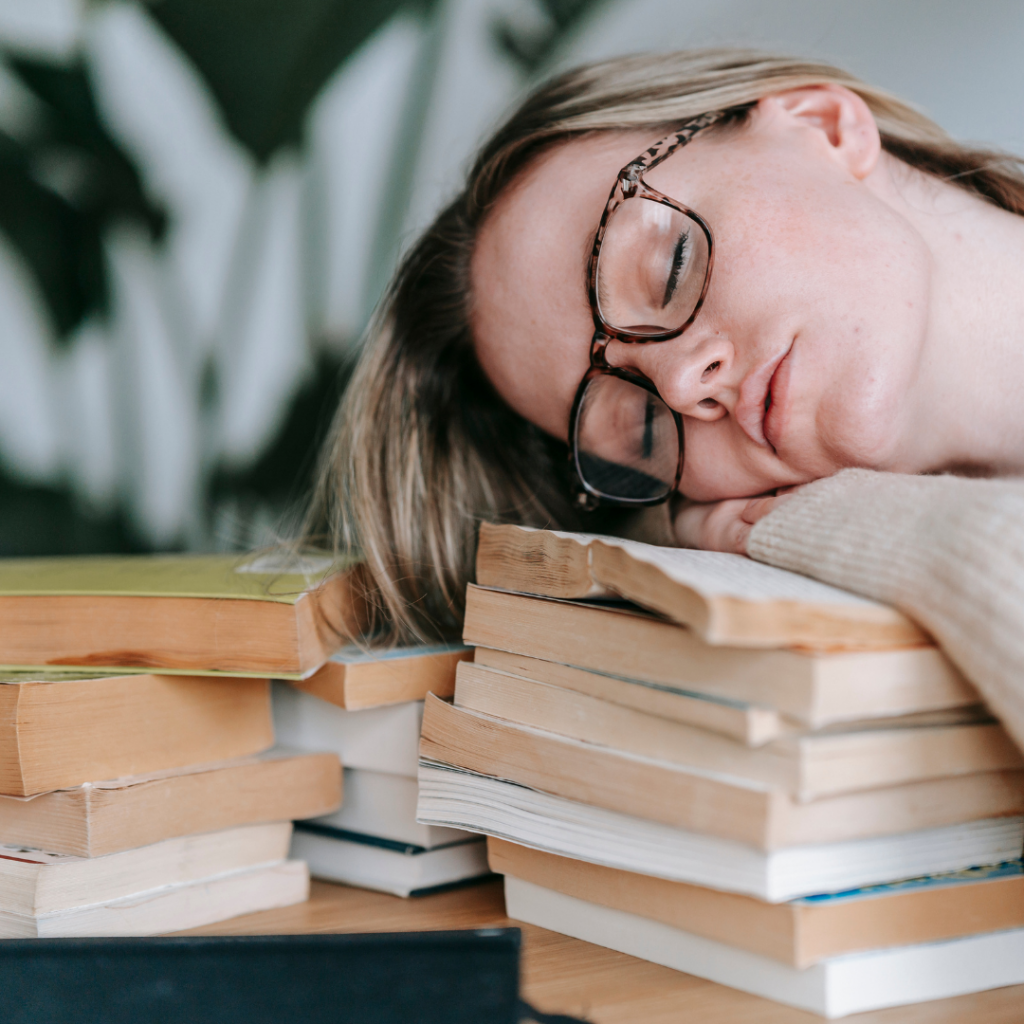 Tired woman with resting her face on a stack of books